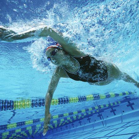 Professional Caucasian female swimmer swimming in pool